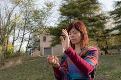 Qi gong exercises. Woman performs qi gong exercises inside a large room Stock Images
