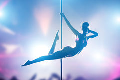 Woman performs sexy pole dance in night club Royalty Free Stock Photos