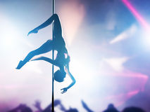 Woman performs sexy pole dance in night club Stock Photography
