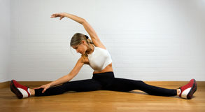 Woman performs splits and side stretch. Middle aged woman in white tanktop and black leggings doing exercise. Stretches legs and left hand side. White tanktop stock images