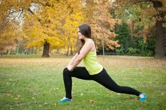 Woman performs stretching before jogging. Outside in nature stock photography