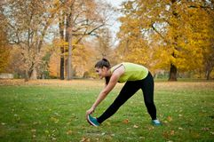 Woman performs stretching before jogging Royalty Free Stock Image