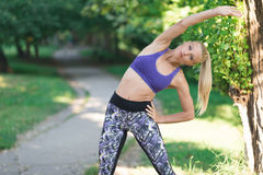 Woman performs stretching before jogging Stock Photography