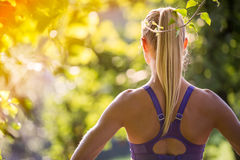 Woman performs stretching before jogging. In park Stock Photos