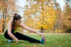 Woman performs stretching before jogging Royalty Free Stock Photo