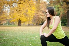 Woman performs stretching before jogging Stock Photos