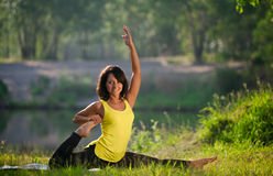 Woman performs yoga exercises and Pilates in nature Stock Photo