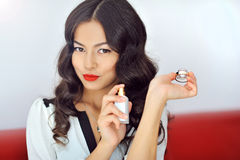 Woman with perfume, young beautiful girl holding bottle of perfu Stock Photography