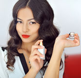 Woman with perfume, young beautiful girl holding bottle of perfu Stock Images