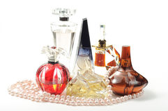 Woman perfumes. On white background with pearl necklace Royalty Free Stock Photos