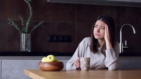 Woman with headache sitting in kitchen stock video