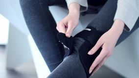 Woman with injured knee wears recovery bandage stock video footage