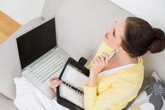 Woman with personal organizer and laptop at home Royalty Free Stock Images