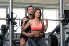 Woman With Personal Trainer At Barbell Squat stock images