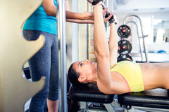 Woman with personal trainer bench pressing with weights, gym Royalty Free Stock Photos