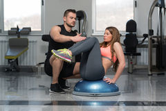Woman With Personal Trainer On Bosu Abs Exercise. Personal Trainer Showing Young Woman How To Train On Bosu Abs Exercise In A Health And Fitness Concept Royalty Free Stock Photography
