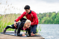 Woman with personal trainer doing fitness push-up Royalty Free Stock Images