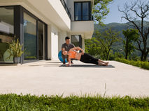 Woman with personal trainer doing morning yoga exercises. Young handsome women with personal trainer doing morning yoga exercises in front of her luxury home Royalty Free Stock Photos