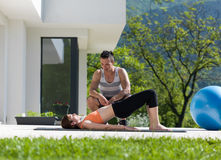 Woman with personal trainer doing morning yoga exercises. Young handsome women with personal trainer doing morning yoga exercises in front of her luxury home Royalty Free Stock Image