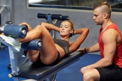 Woman with personal trainer doing sit ups in gym Stock Images