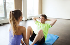 Woman with personal trainer doing sit ups in gym Royalty Free Stock Photos
