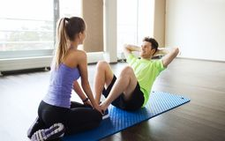 Woman with personal trainer doing sit ups in gym Royalty Free Stock Photography