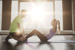Woman with personal trainer doing sit ups in gym Royalty Free Stock Photo