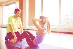 Woman with personal trainer doing sit ups in gym Royalty Free Stock Images
