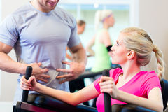 Woman with personal trainer doing sport stock photography