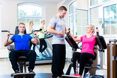 Woman with personal trainer doing sport. In gym Royalty Free Stock Images