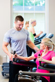 Woman with personal trainer doing sport Stock Photo