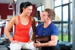 Woman and Personal Trainer in fitness gym Stock Image
