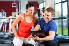 Woman and Personal Trainer in fitness gym Stock Photo