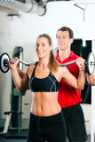 Woman with Personal Trainer in gym stock image