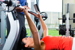Woman and Personal Trainer in gym Royalty Free Stock Photography