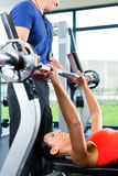 Woman and Personal Trainer in gym Royalty Free Stock Images
