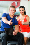 Woman and Personal Trainer in gym, with dumbbells stock images