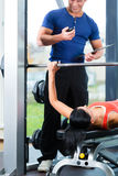 Woman and Personal Trainer in gym Stock Image