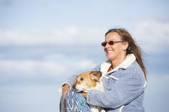 Woman with pet dog friend happy outdoor. Portrait of attractive mature woman sitting outdoor with pet dog friend relaxed on sunny day, with sky as blurred Stock Photos