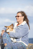Woman with pet dog friend relaxed outdoor. Portrait of attractive mature woman sitting outdoor with pet dog friend relaxed on sunny day at beach, with ocean and Royalty Free Stock Image