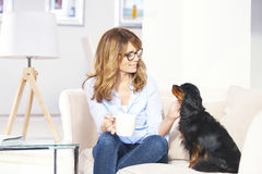 Woman with pet dog at home. Shot of a happy mature woman enjoying time with her pet dog while sitting of sofa at home and relaxing Royalty Free Stock Image