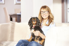 Woman with pet dog at home. Shot of a happy mature woman enjoying time with her pet dog while sitting of sofa at home and relaxing Royalty Free Stock Photo