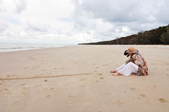 Woman and pet dog sitting on beautiful deserted beach Stock Photo