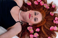 The woman with petals of times on Stock Photography