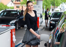 Woman in petrol station. Woman holding fuel nozzle and refuel car in gas station Royalty Free Stock Photo