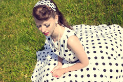 Woman with a petticoat dress, a braid and a suicide roll sitting Royalty Free Stock Photography