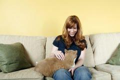 Woman petting cat. Orange tabby sitting on a pretty woman's lap Royalty Free Stock Image