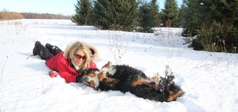 Woman petting her dog in snow Stock Photo