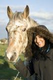Woman petting horse Stock Photo