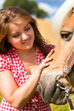 Woman petting horse on farm Stock Image
